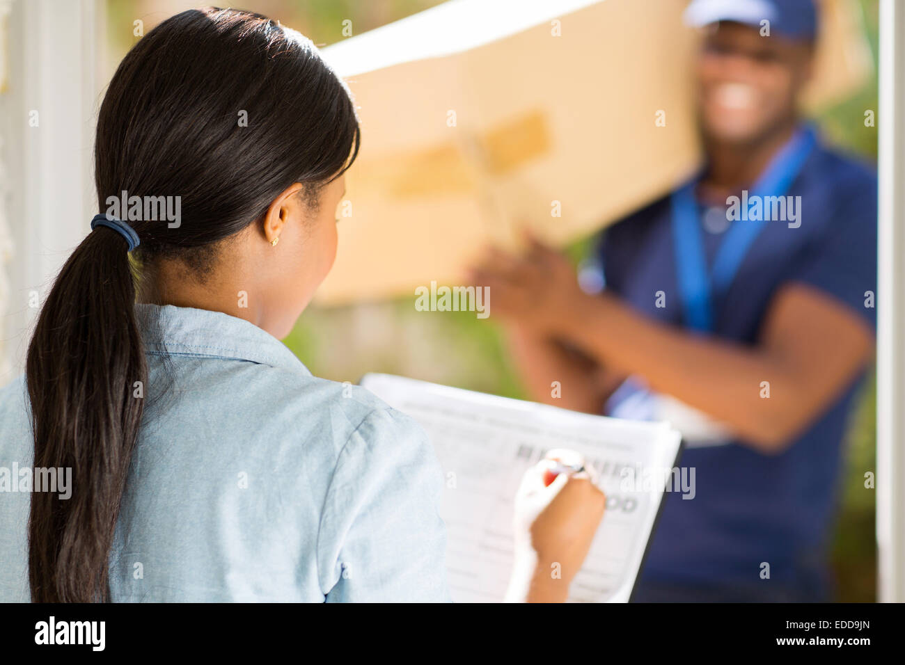 rear view African woman signing receiving paper from courier guy - Stock Image
