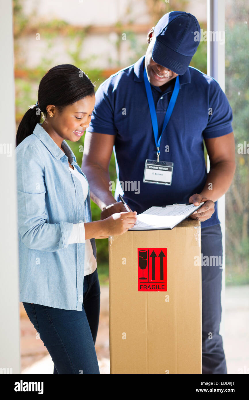 beautiful customer signing for delivery from courier - Stock Image