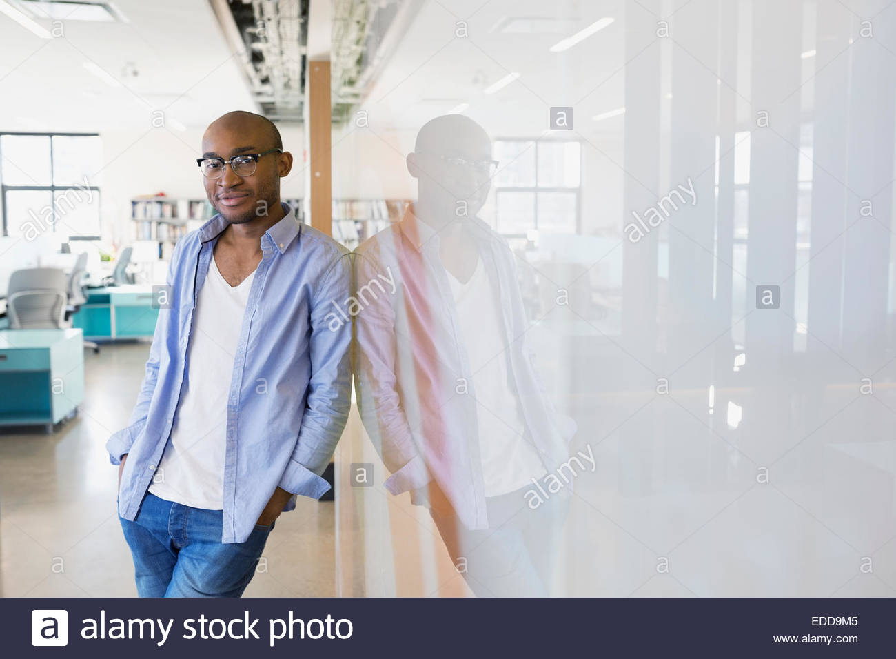 Portrait of confident businessman leaning against whiteboard - Stock Image