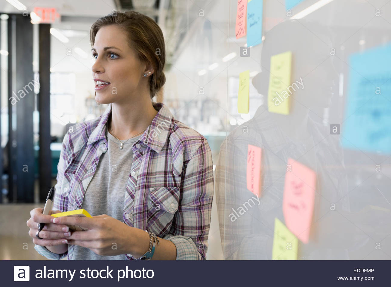 Businesswoman writing adhesive notes on whiteboard - Stock Image
