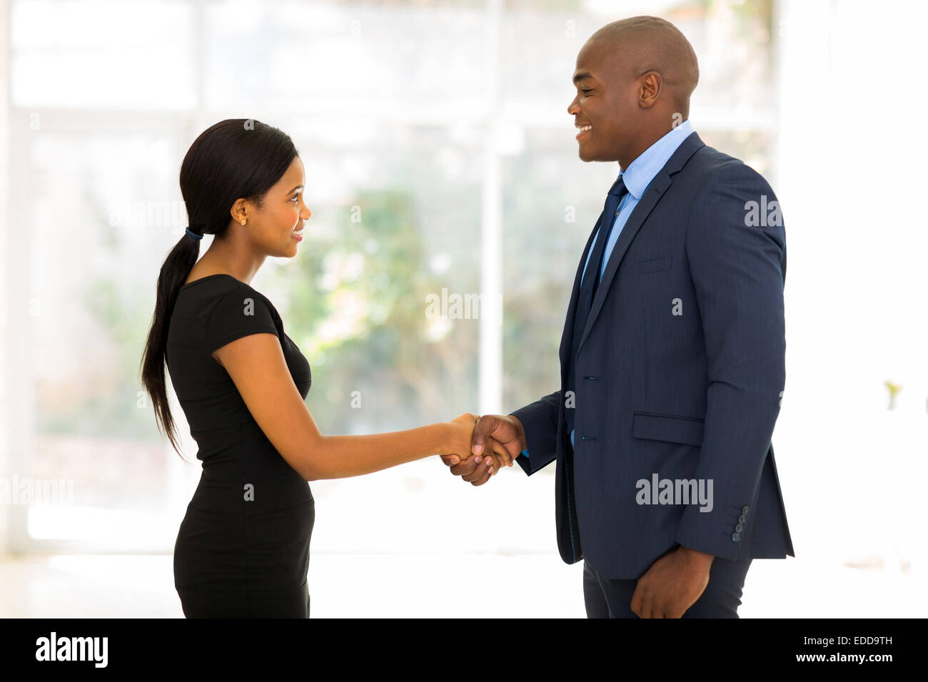 smiling African businessman handshaking with young businesswoman in office - Stock Image