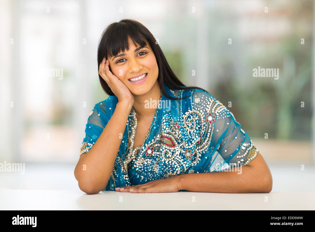 beautiful Indian woman sitting at home - Stock Image