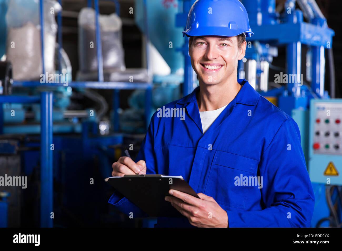 male industrial technician working inside a factory Stock Photo