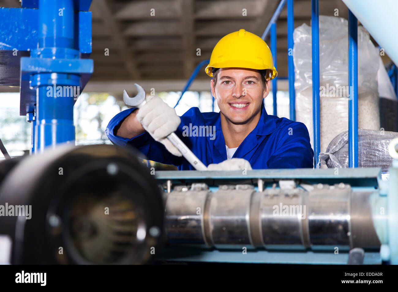 happy modern blue collar worker in factory - Stock Image
