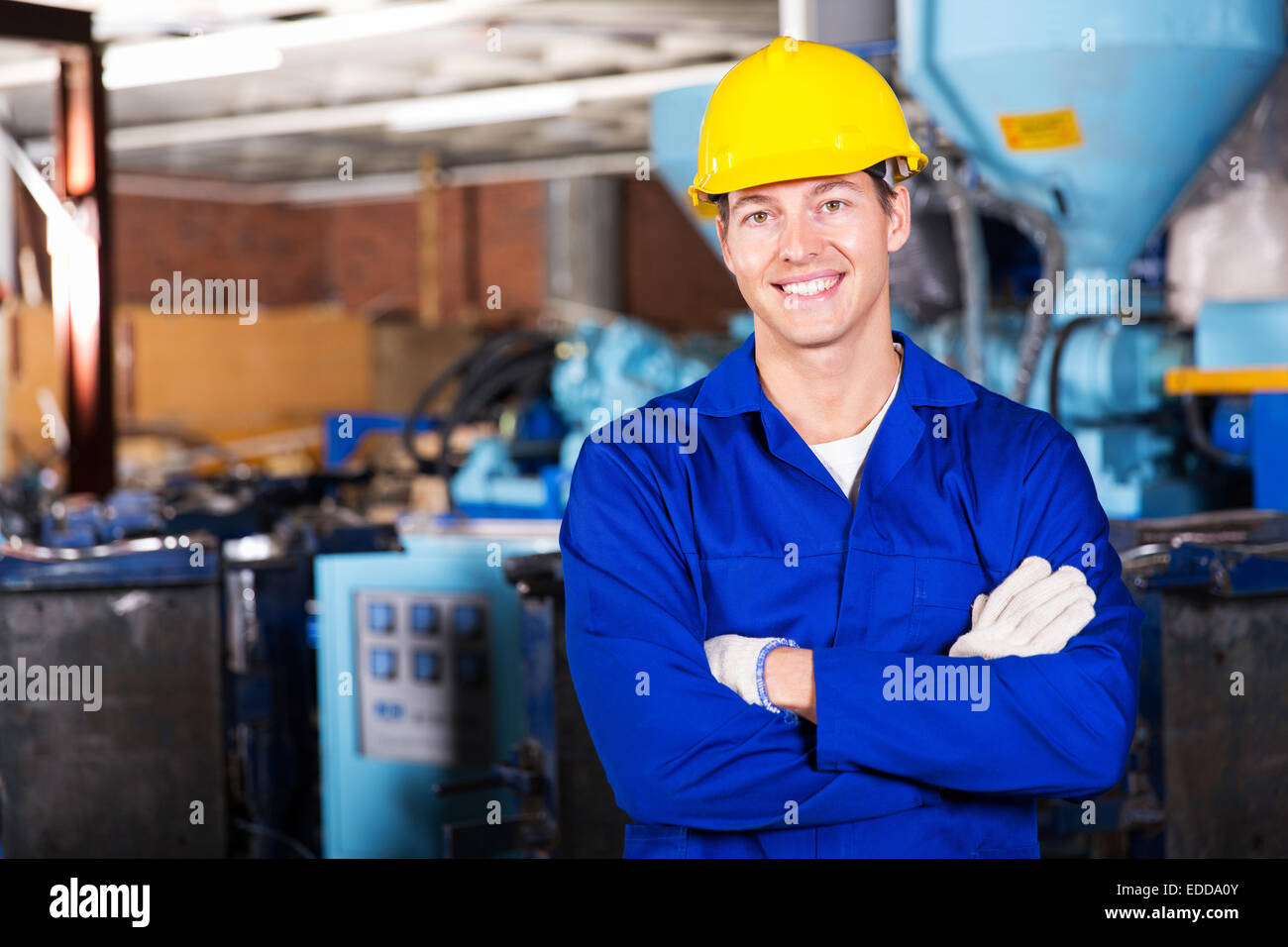 good looking blue collar worker in factory - Stock Image