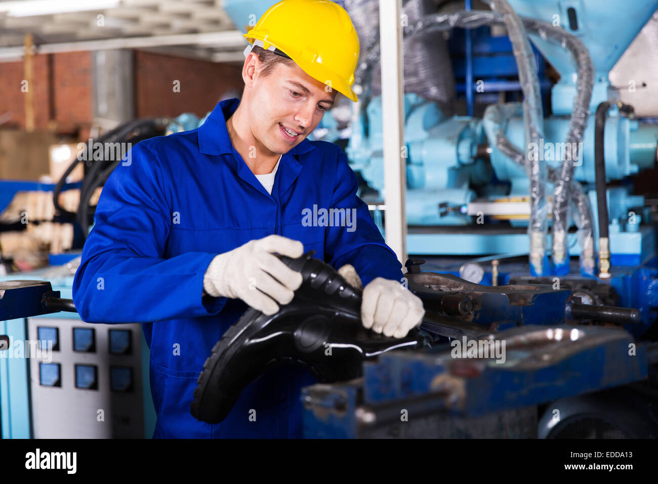 skilled man working in a gumboot factory - Stock Image