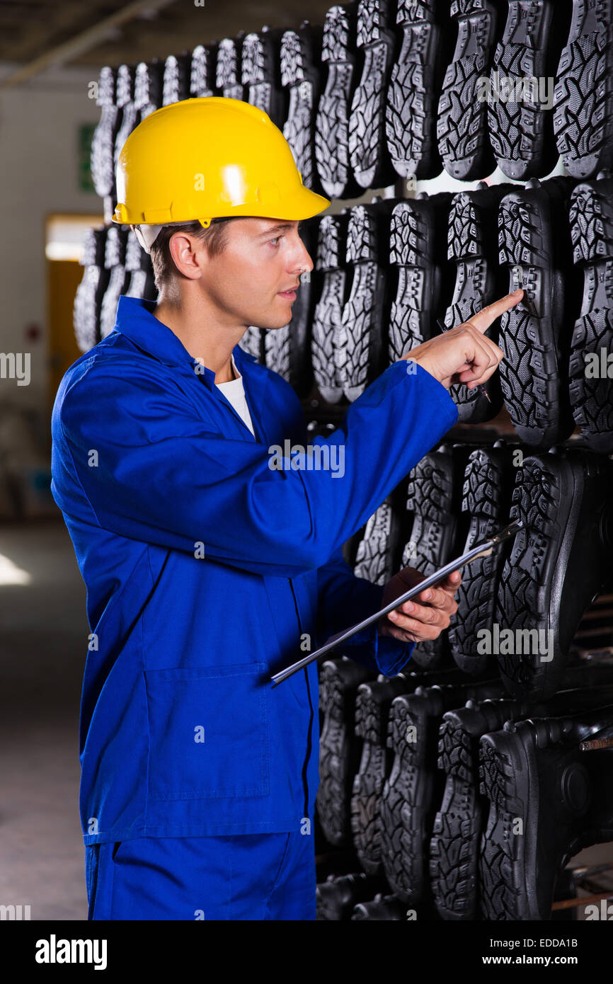 quality controller checking quality of gumboots - Stock Image