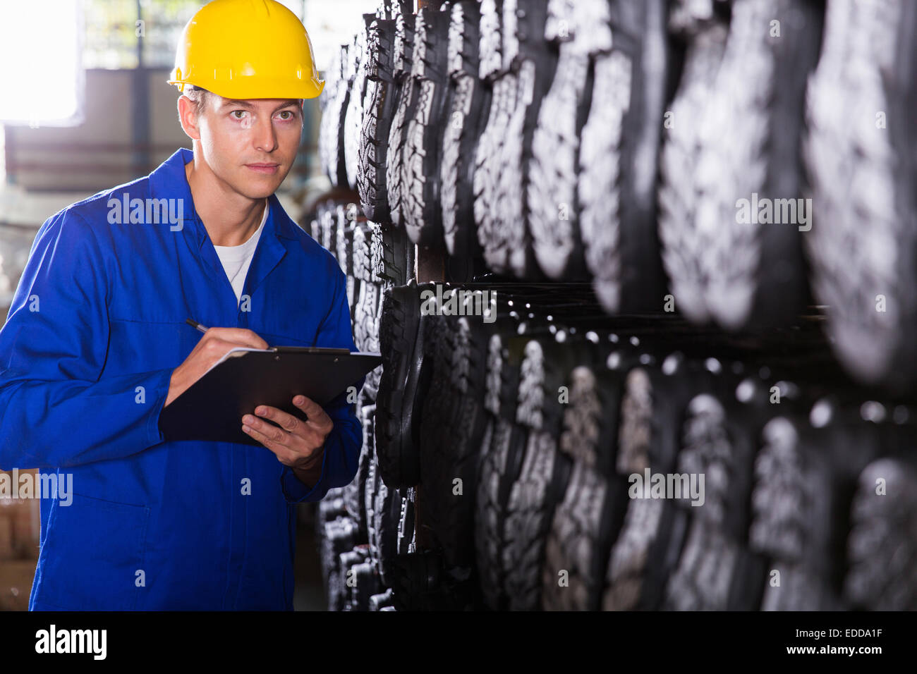 factory quality controller checking gumboots in warehouse - Stock Image