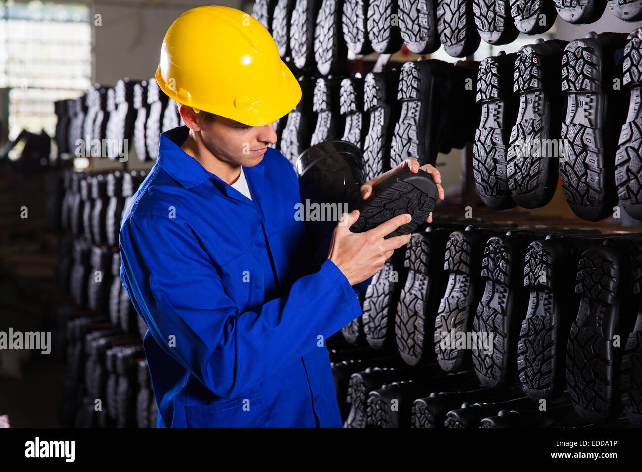 quality controller checking rubber-boots sole in storeroom - Stock Image