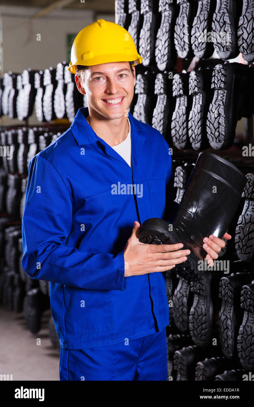 smiling factory worker holding rubber-boot - Stock Image