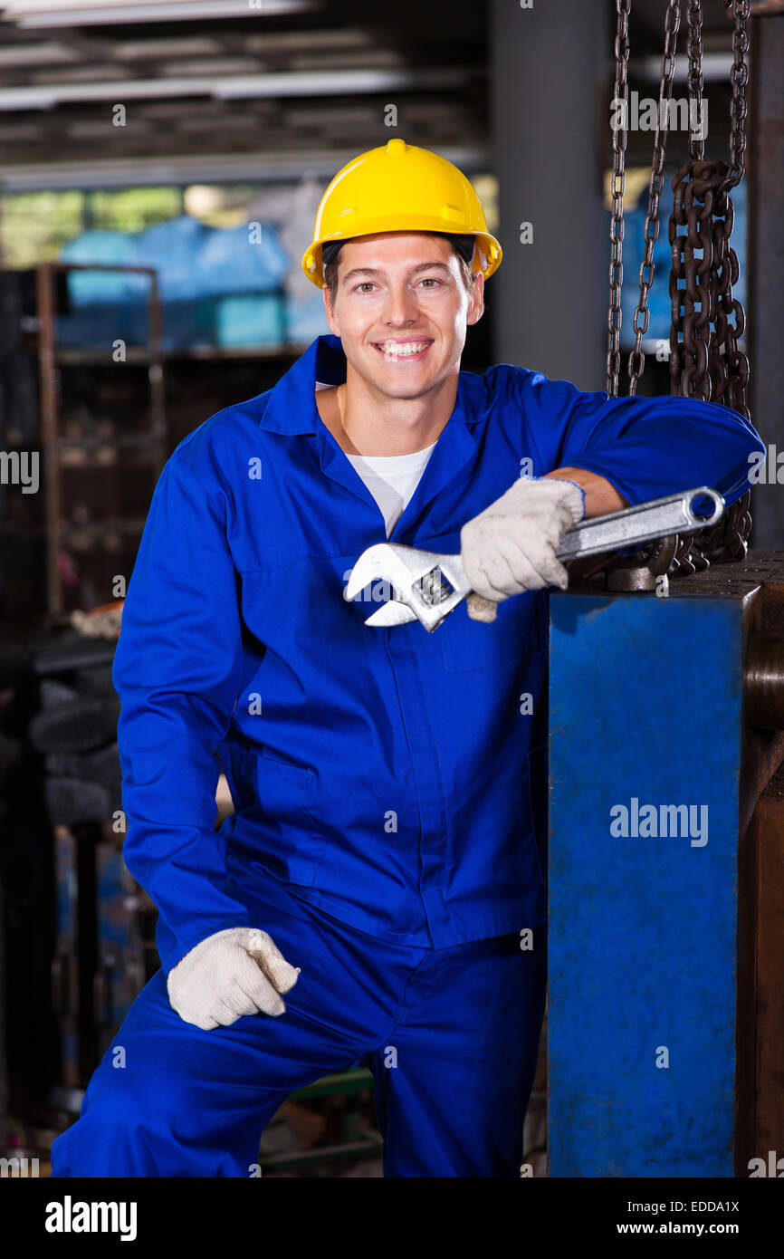 male manual worker holding spanner in factory - Stock Image