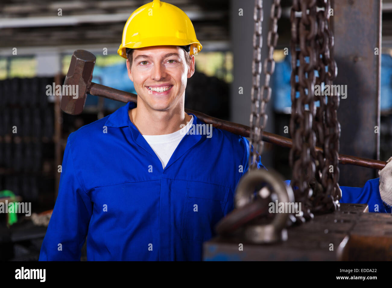 happy male manual worker in factory - Stock Image