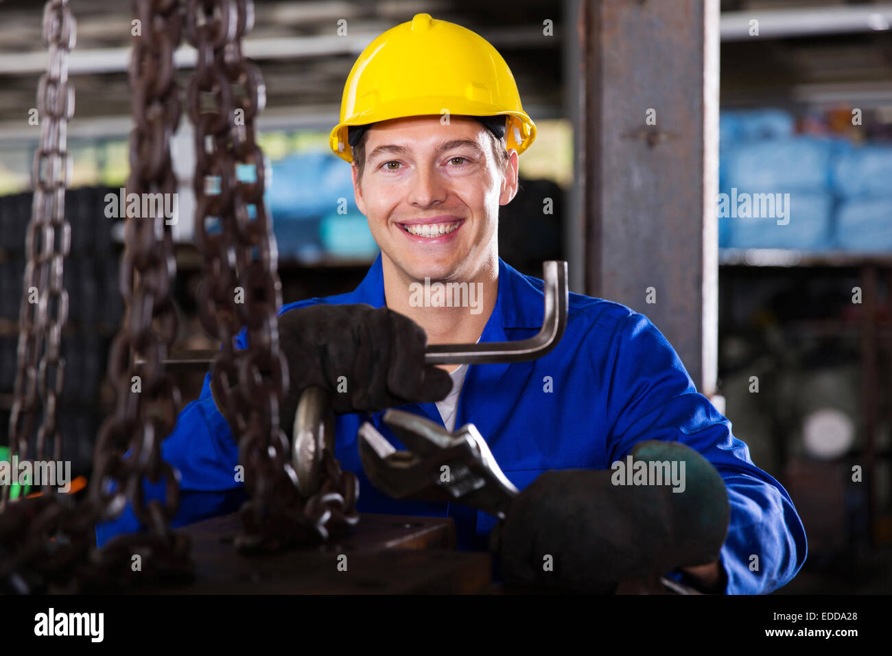 happy blue collar worker with tools in workshop - Stock Image