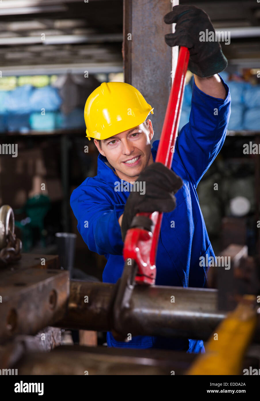 manual worker using wrench on industrial machine - Stock Image