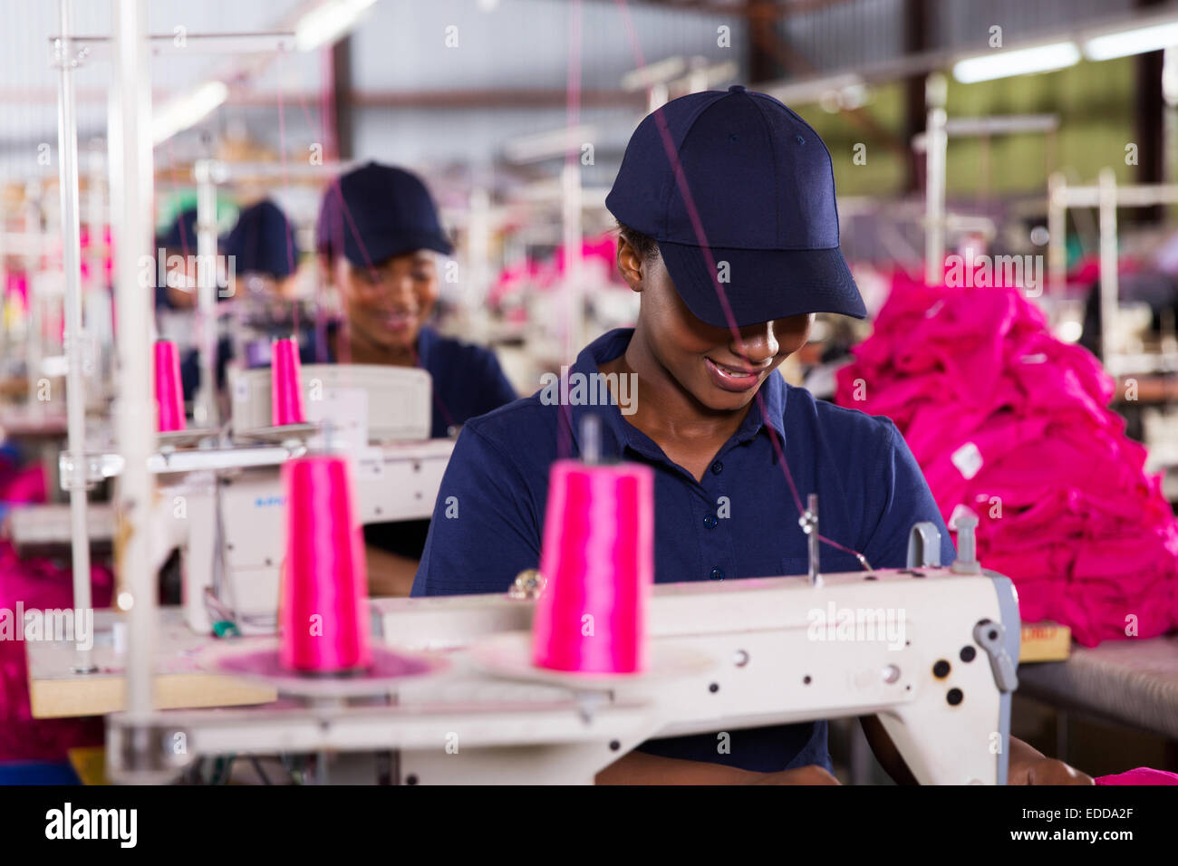 smiling African worker sewing in clothing factory - Stock Image