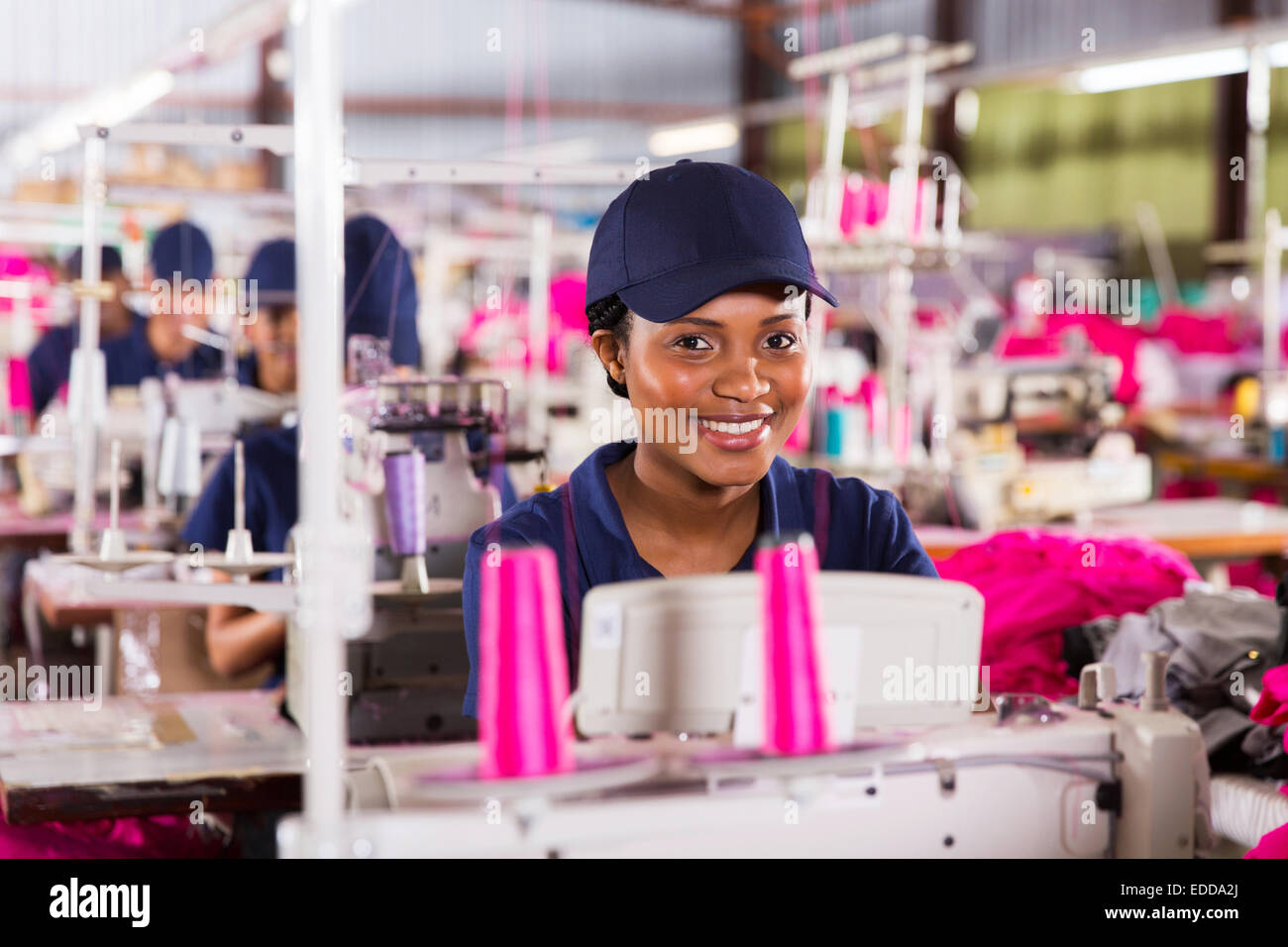 pretty African textile worker sewing - Stock Image