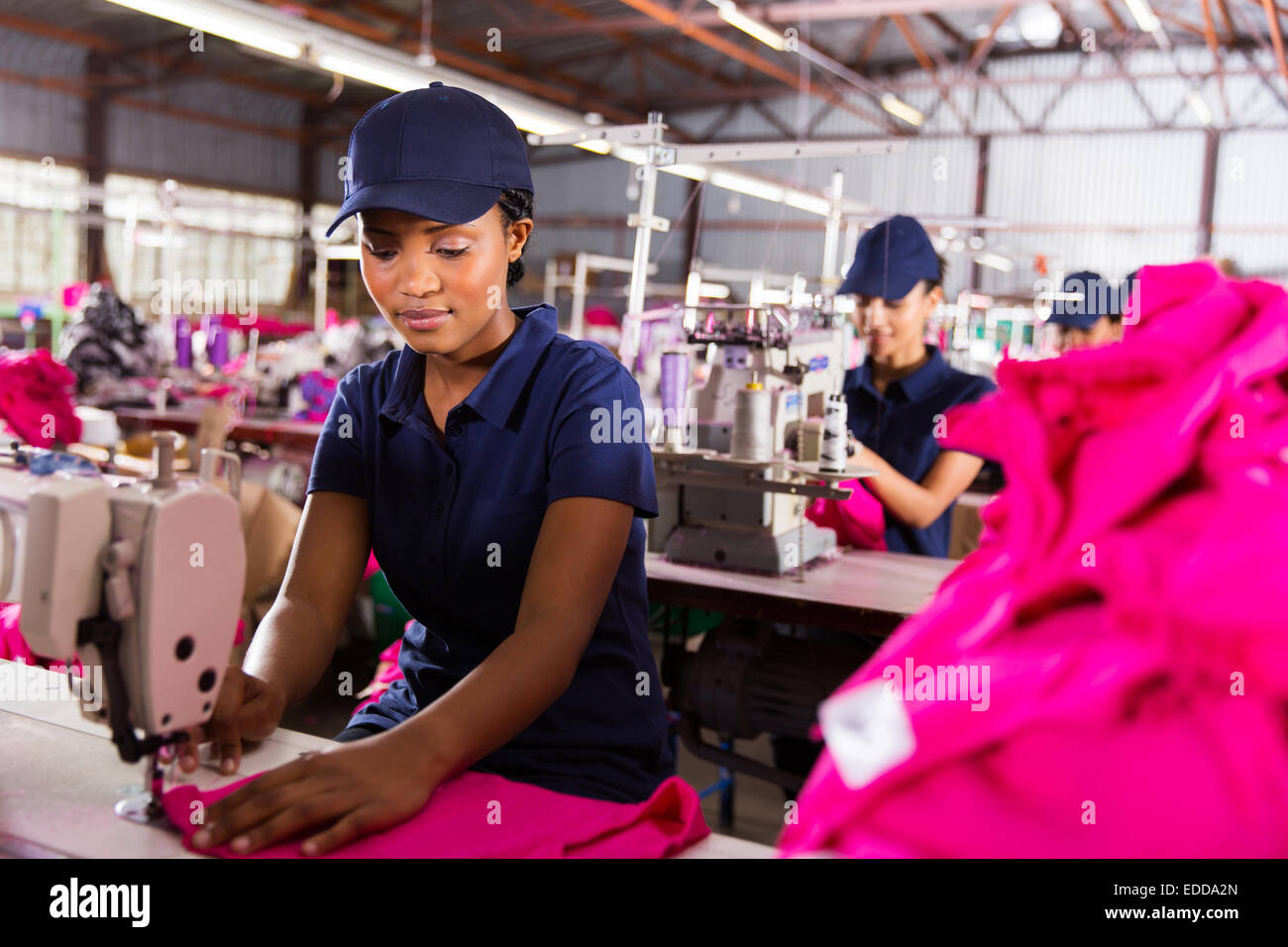 female factory worker sewing with colleagues on background - Stock Image
