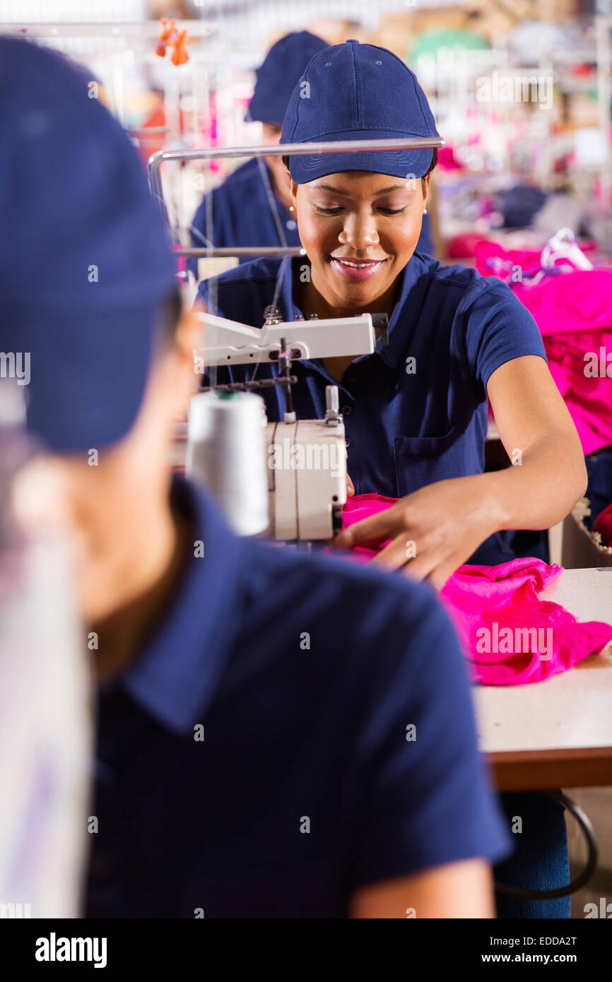 beautiful African textile worker using sewing machine - Stock Image