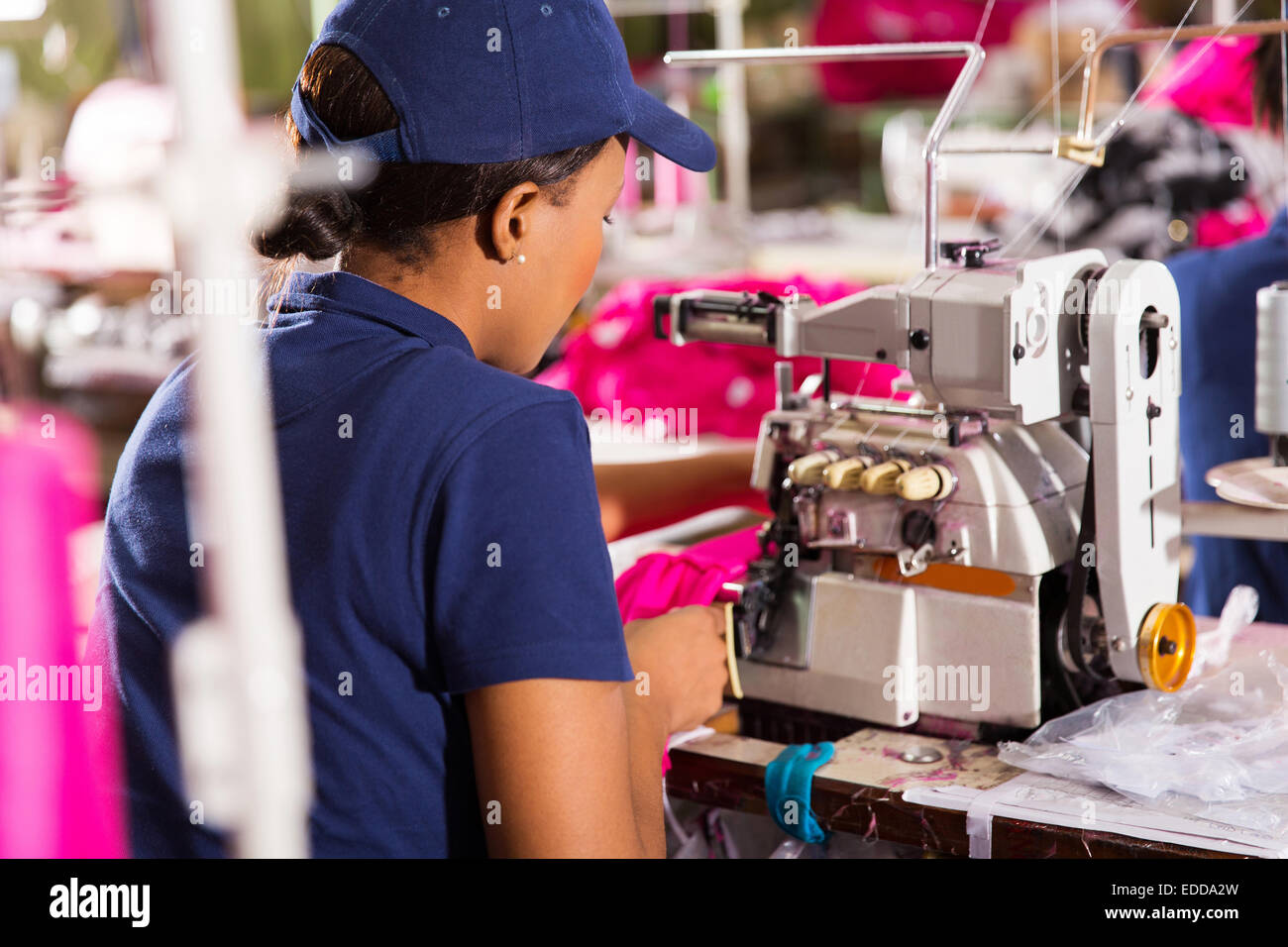 rear view of textile worker sewing - Stock Image