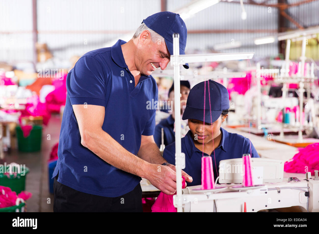 clothing factory quality controller checking stitch on production line - Stock Image