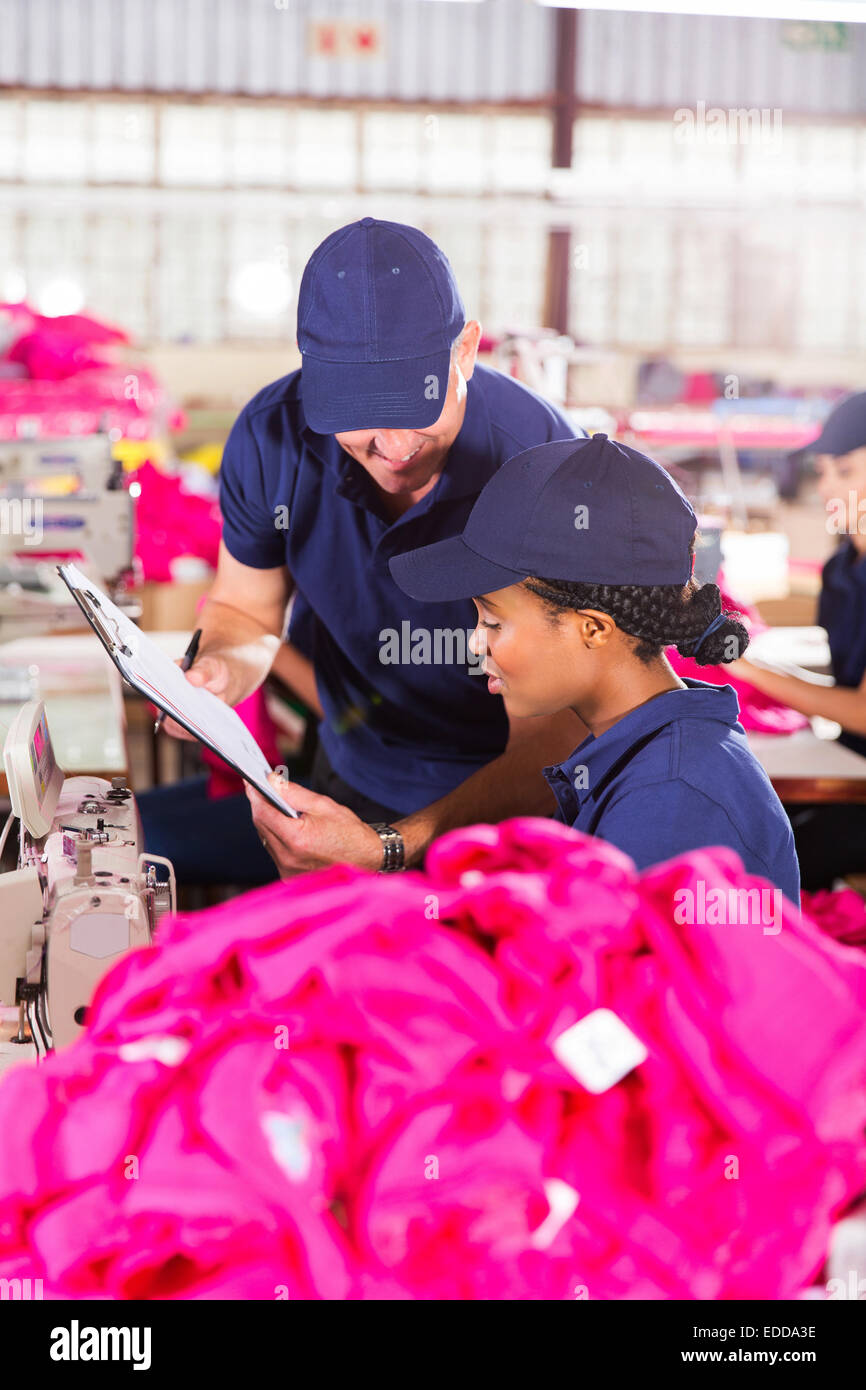 foreman and dressmaker looking at clipboard in factory - Stock Image