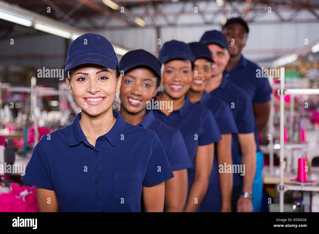 group of machinists line up in clothing factory - Stock Image