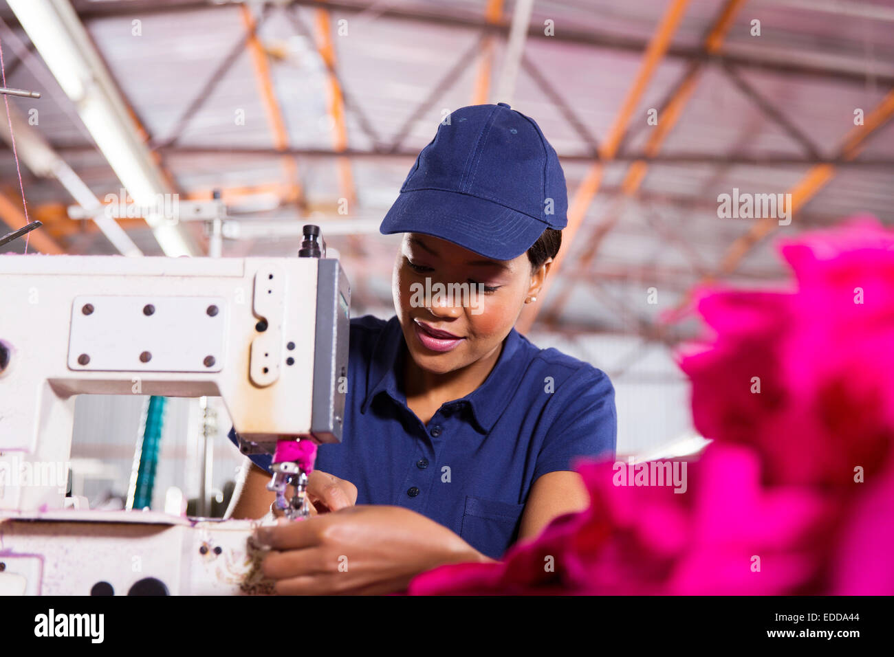 pretty young African worker sewing in clothing factory - Stock Image