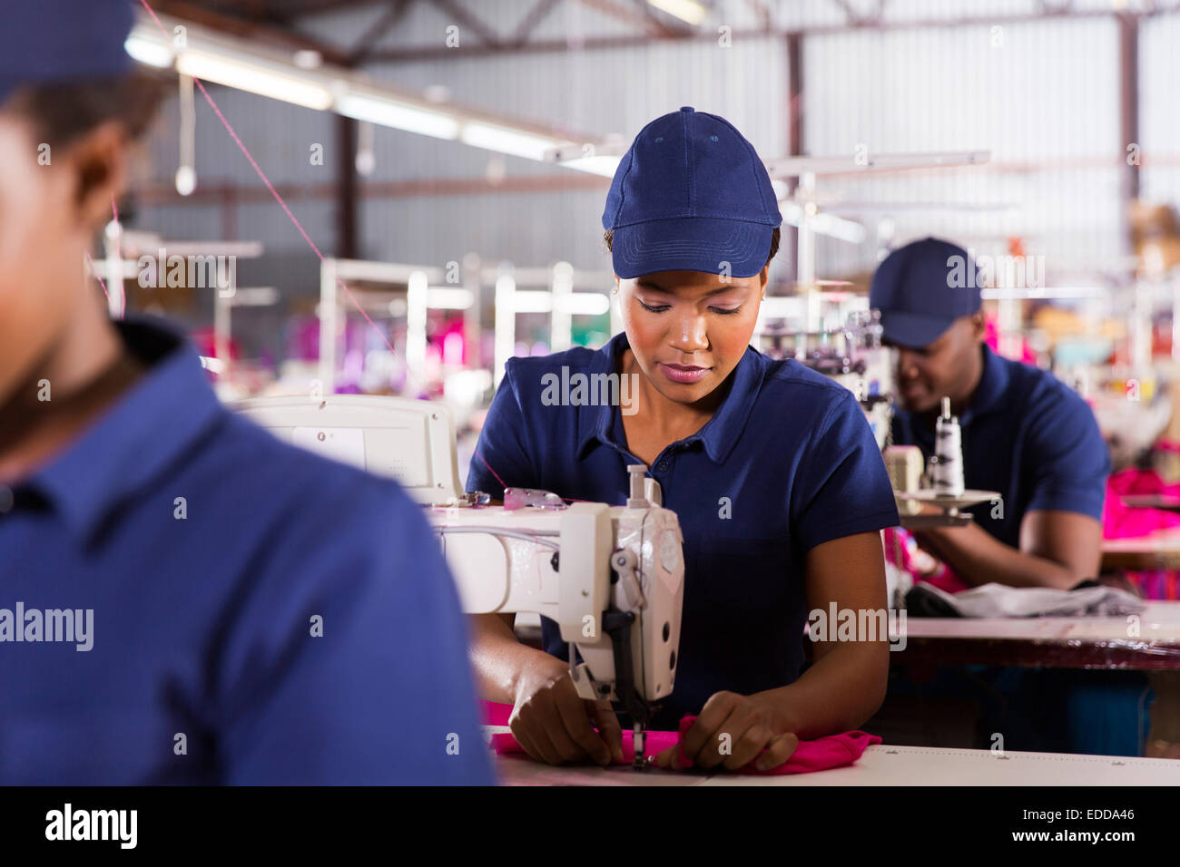 African textile factory machinist working in production line - Stock Image