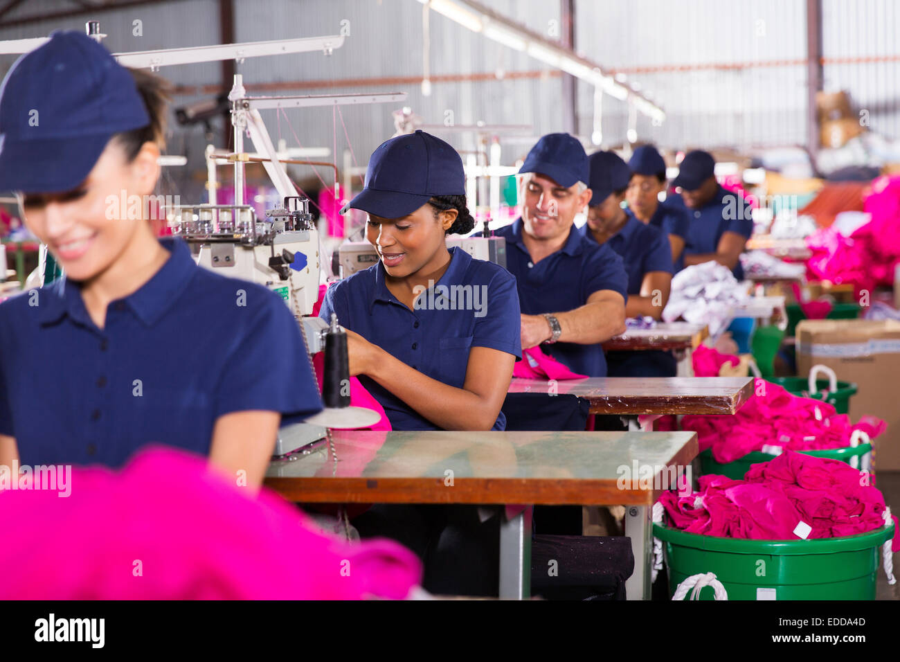 group multiracial factory workers sewing in clothing factory - Stock Image