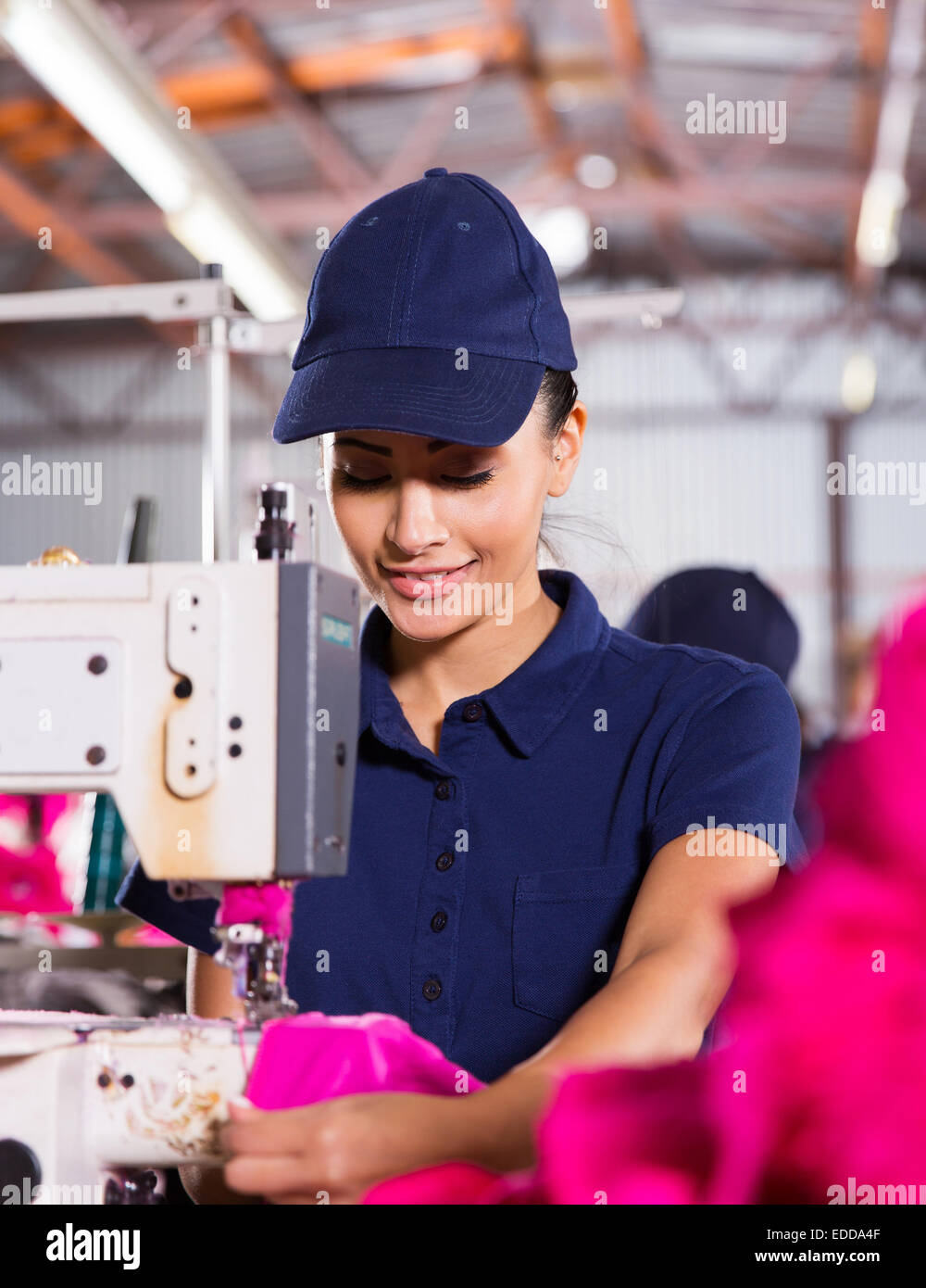 pretty female factory worker sewing garment - Stock Image