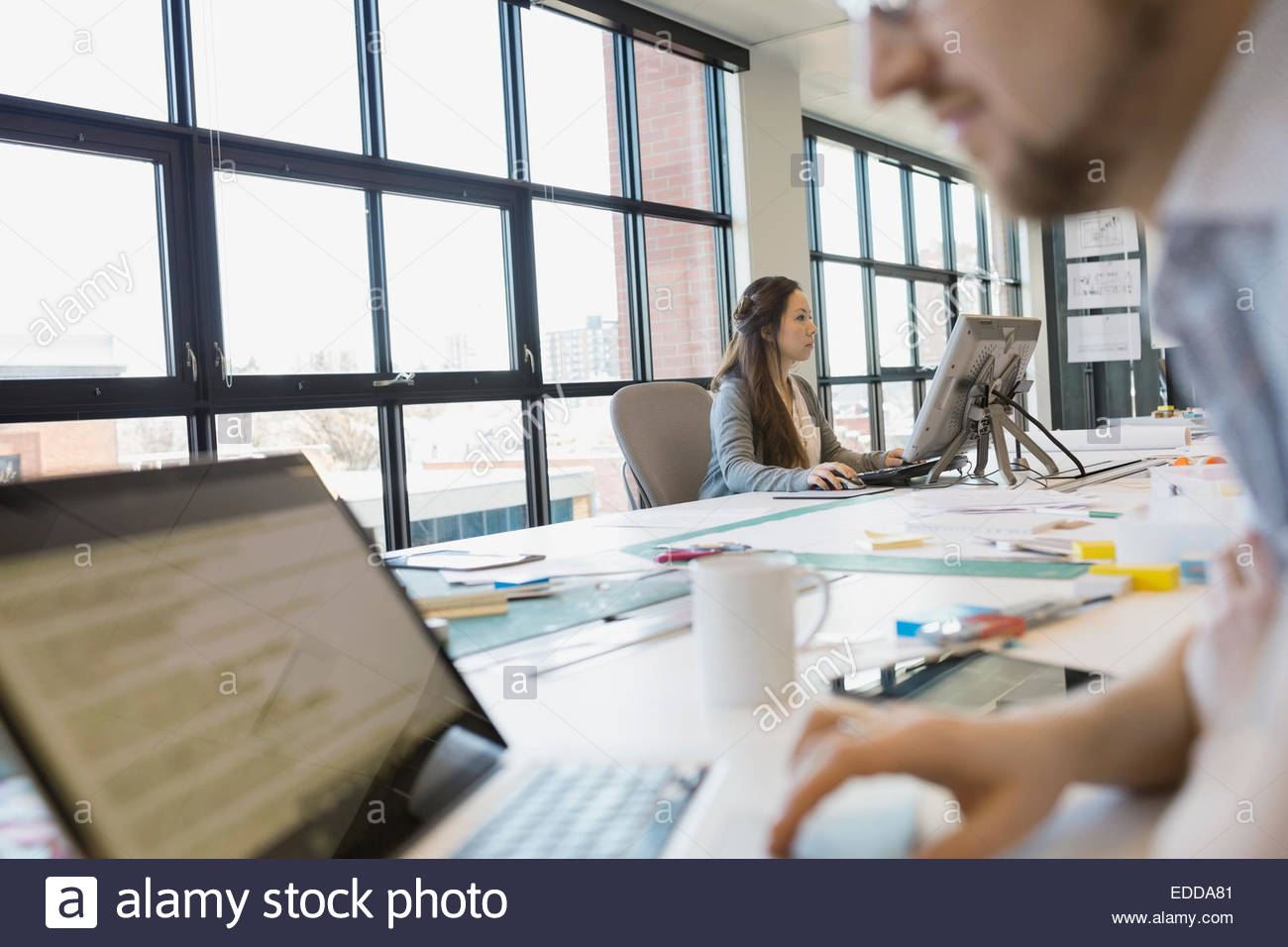 Business people working at computers in office - Stock Image