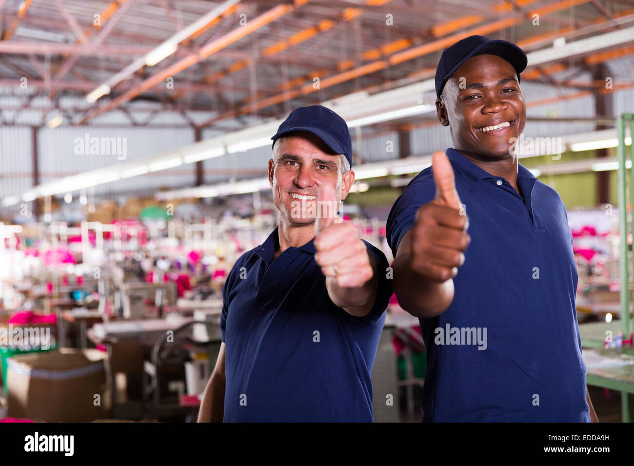 cheerful factory supervisors giving thumbs up - Stock Image