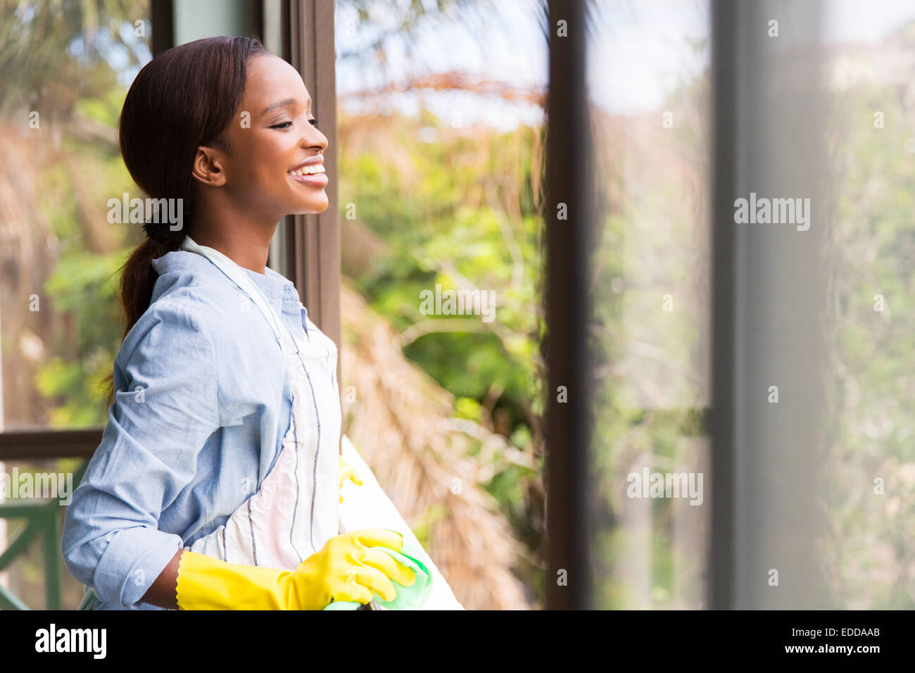 cheerful young African housewife looking through the window - Stock Image