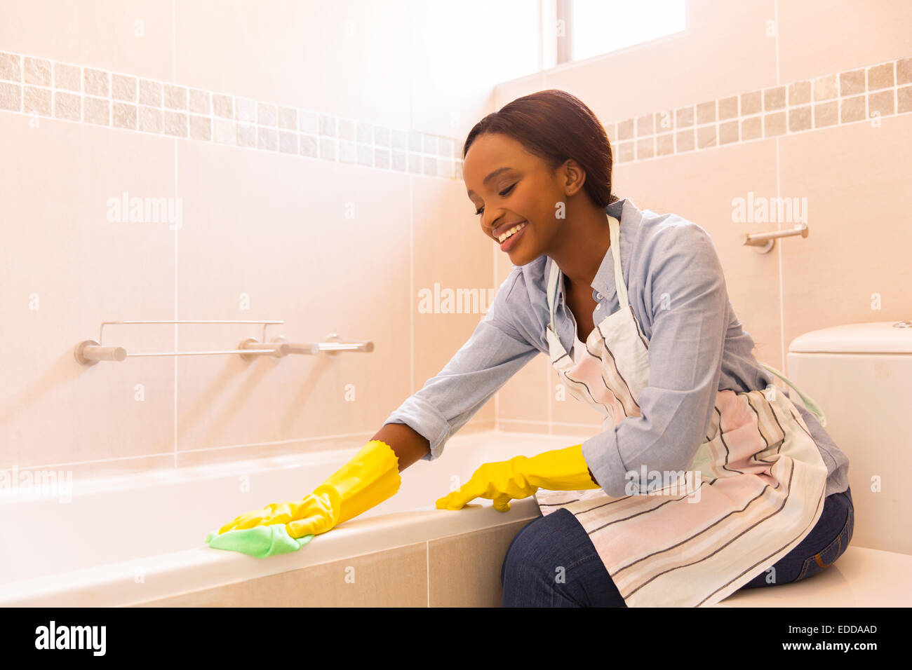 Merveilleux Beautiful Young African Woman Cleaning Bathtub With A Cloth