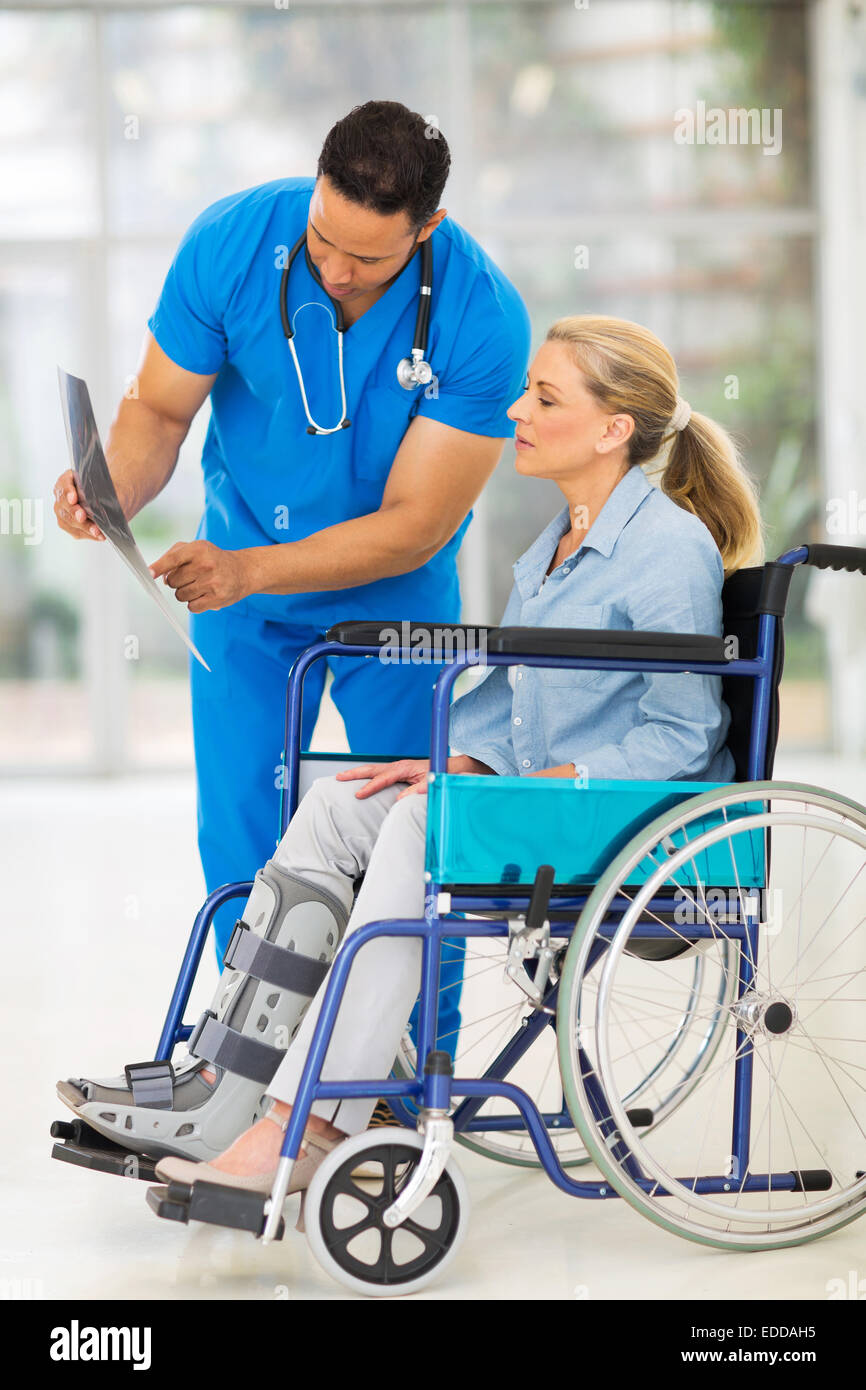 doctor explaining x-ray results to patient in wheelchair - Stock Image