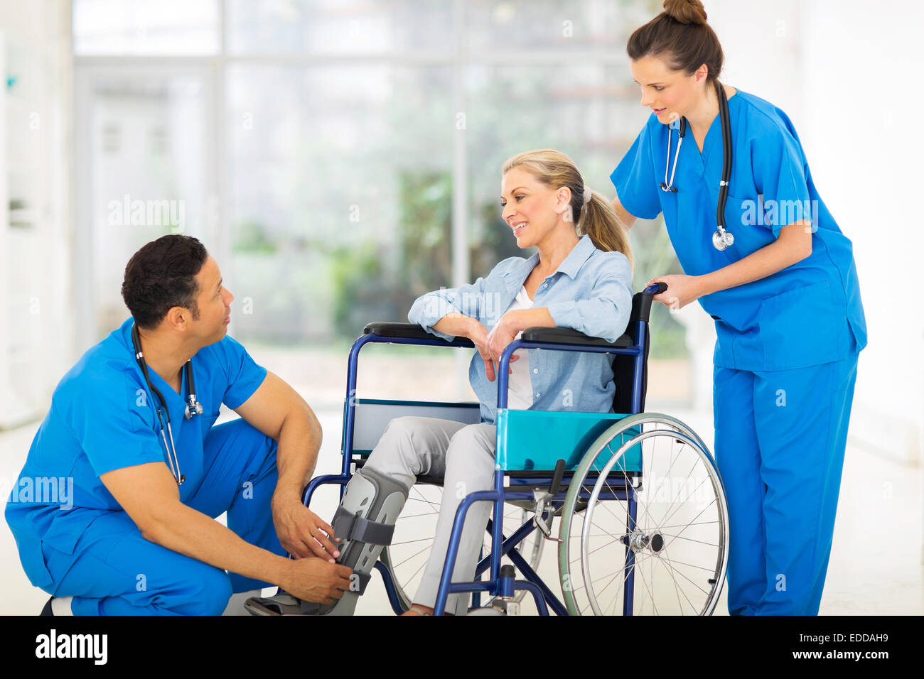 friendly doctor talking to a recovering patient in wheelchair - Stock Image