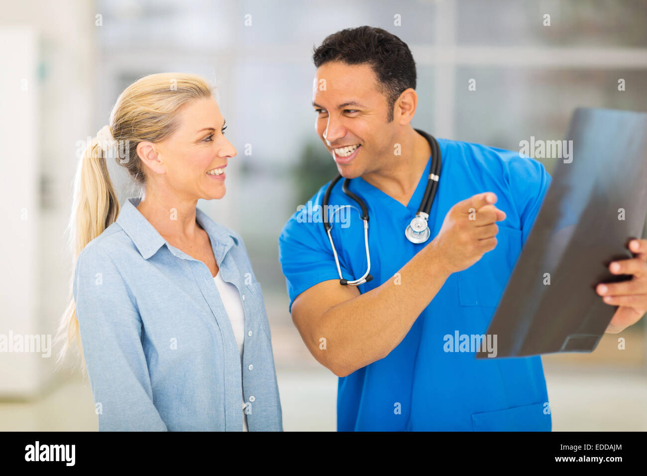 happy doctor and senior patient looking at x-ray result in hospital - Stock Image