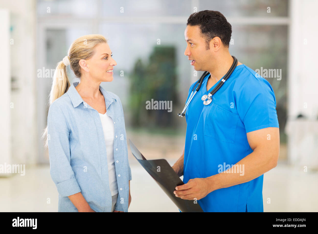 handsome mid age doctor discussing x-ray results to patient - Stock Image