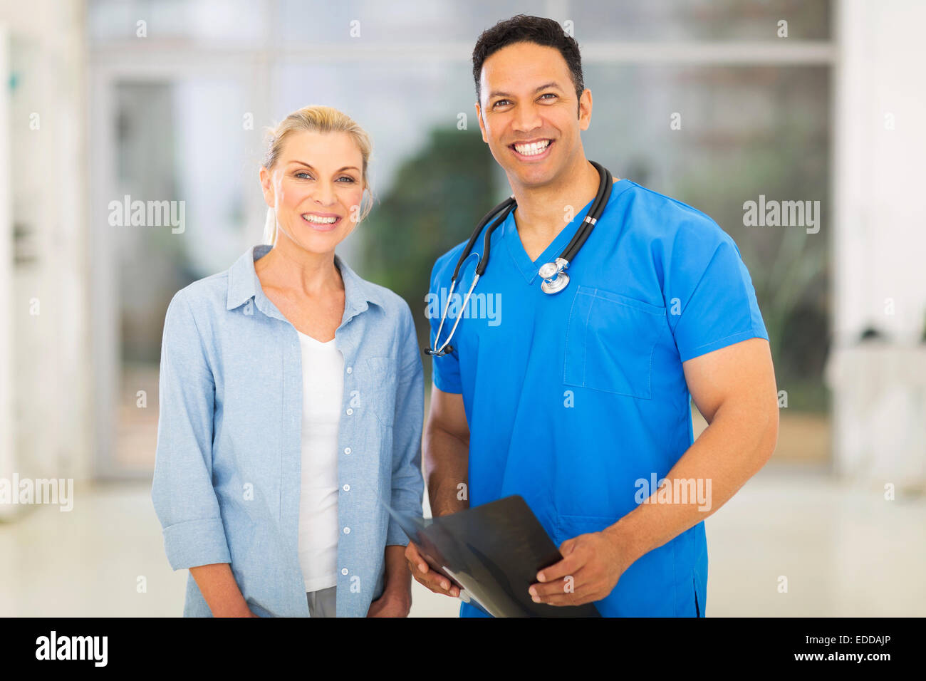 portrait of friendly medical doctor standing with senior patient - Stock Image
