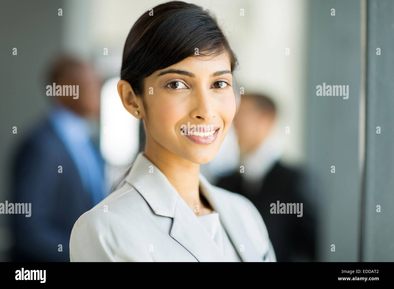 happy female Indian business executive in modern office - Stock Image