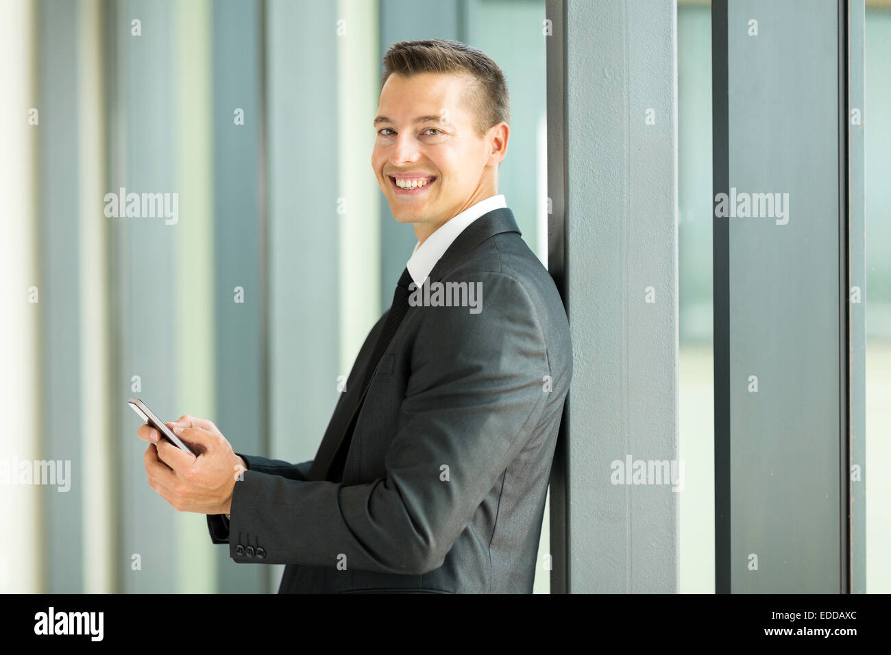 smiling businessman reading email on smart phone - Stock Image