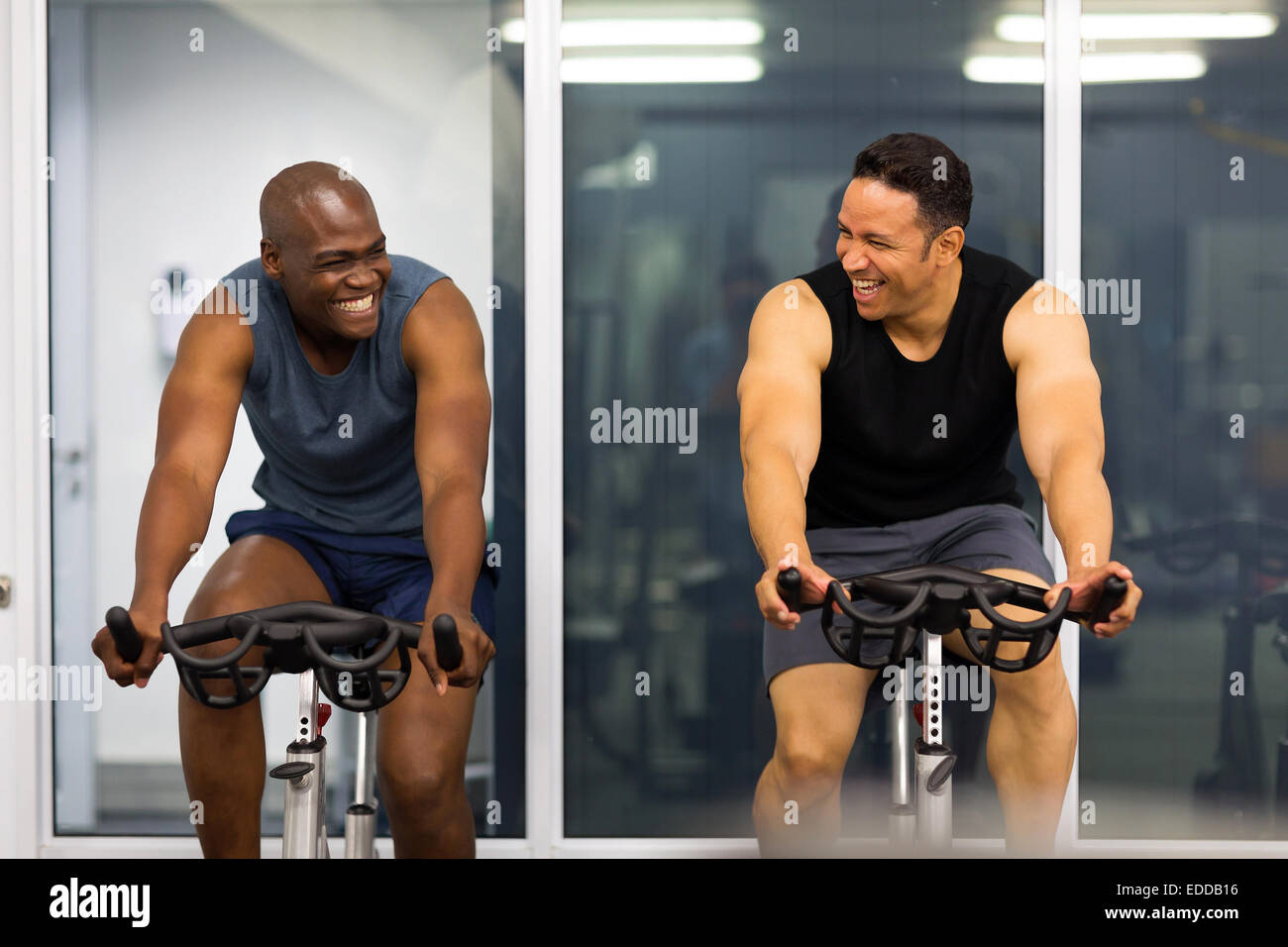 cheerful men working out in gym - Stock Image