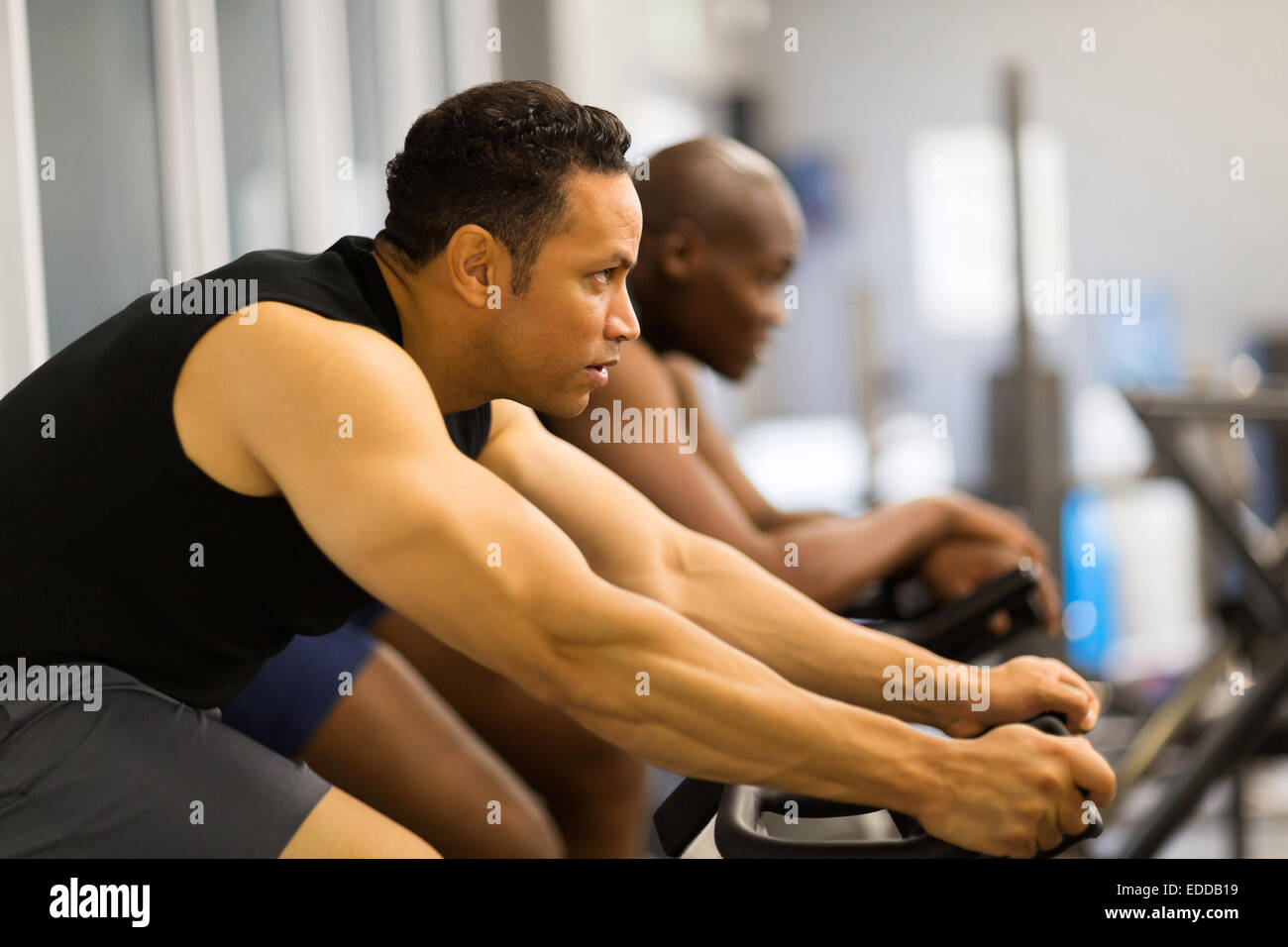 fitness men working out with stationary bike in gym - Stock Image
