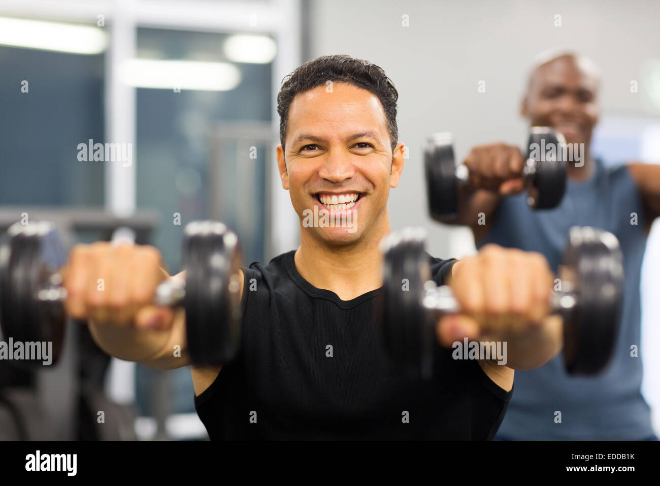 portrait of healthy man working out with dumbbells - Stock Image