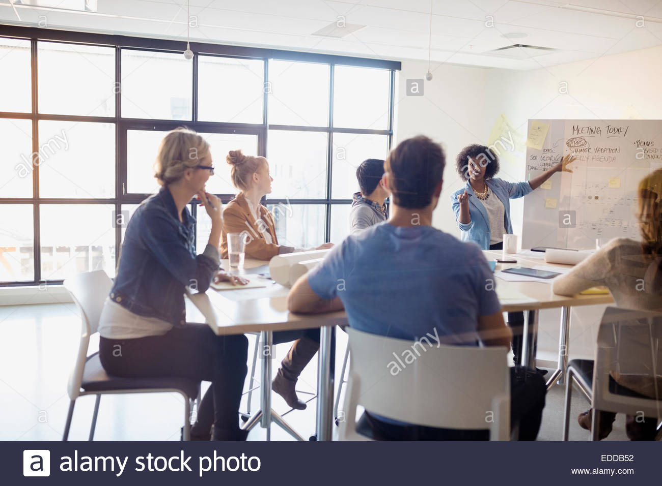 Businesswoman At Whiteboard Leading Meeting In Conference Room Stock - Whiteboard conference table
