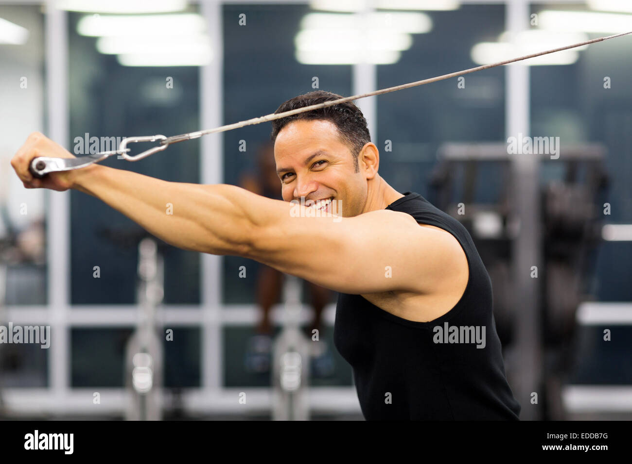 side view of mid age man working out with pull-down machine - Stock Image