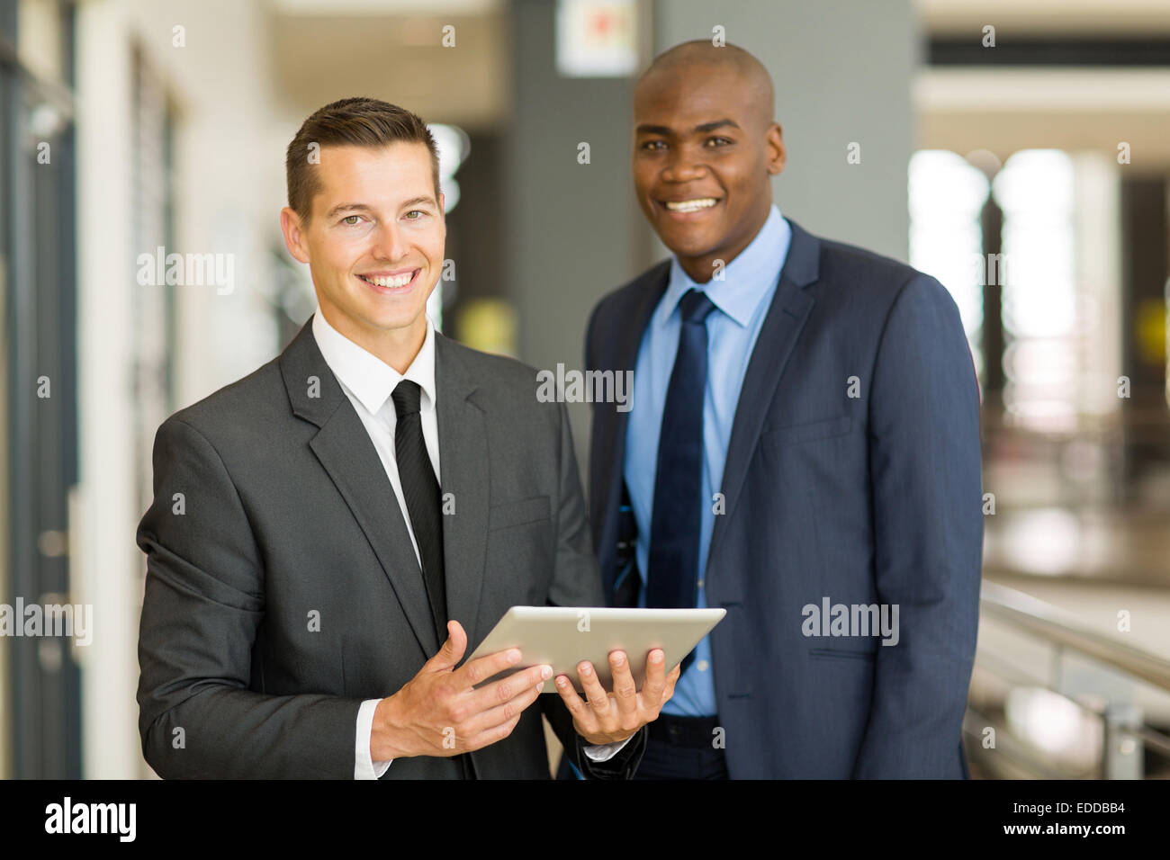 two handsome businessmen using tablet pc in modern office - Stock Image