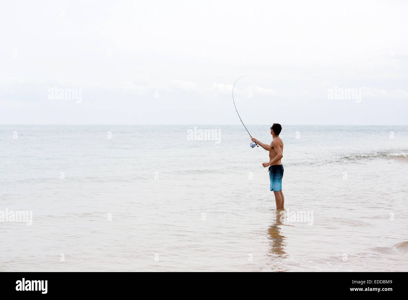 young man fly fishing on beach - Stock Image