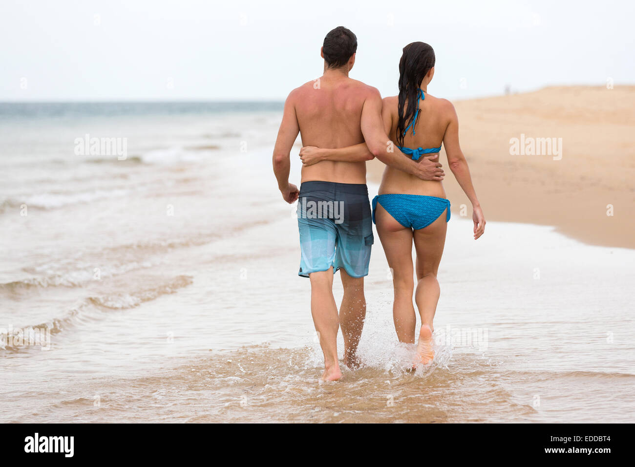 back view of couple walking on beach together - Stock Image