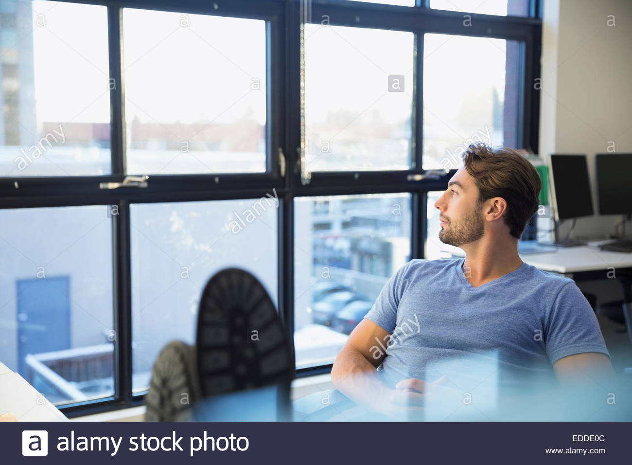 Pensive businessman with feet up looking out window - Stock Image